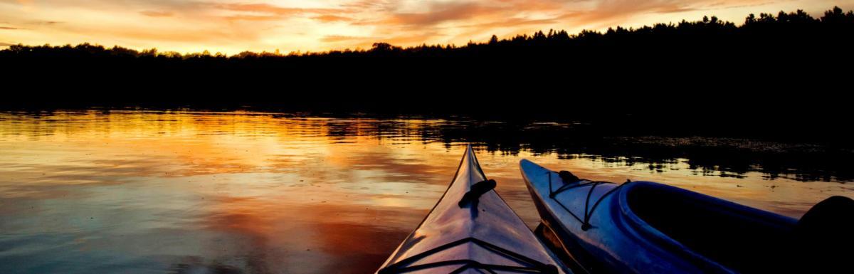 Two kayaks on lake at sunset