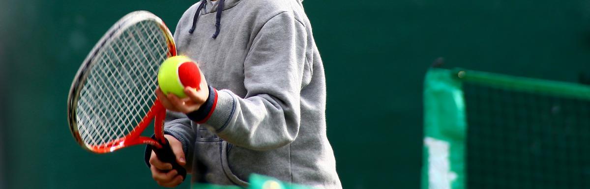Closeup of Kid Holding Tennis Ball and Racquet