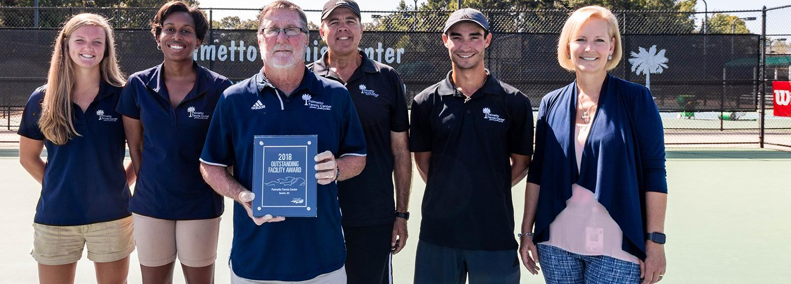 Palmetto Tennis Center Staff Pose with Award Plaque