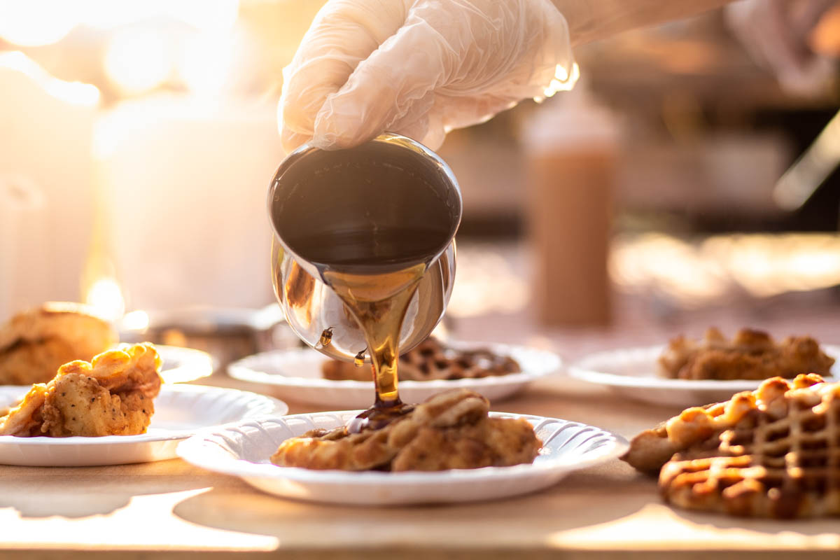 Syrup Being Poured Over Chicken & Waffles