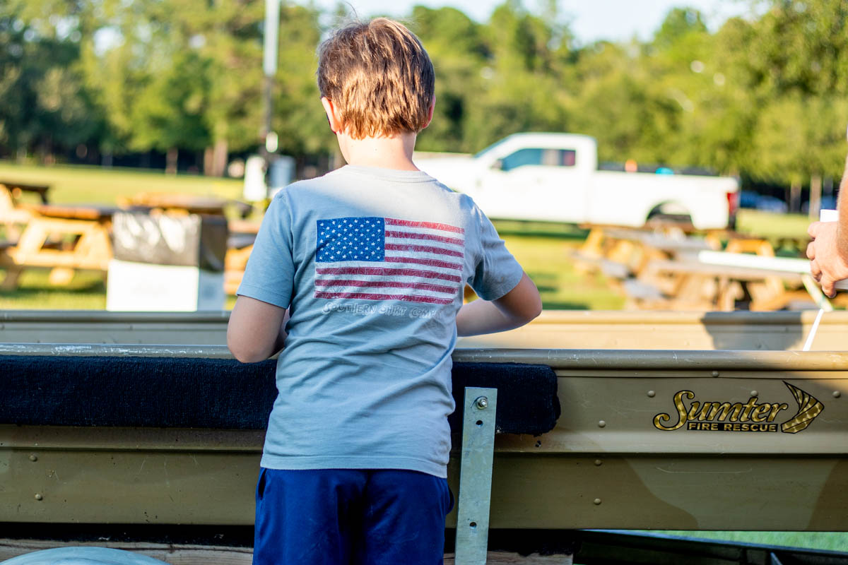 Boy in American Flag Shirt Standing at John Boat